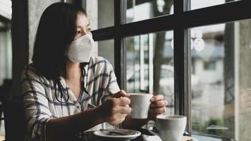 Eine Frau, die eine medizinische Maske trägt, sitzt in einem Café und schaut mit traurigen Augen aus dem Fenster. foto