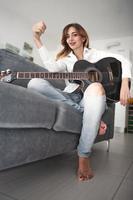 eine junge Linkshänderin mit Akustikgitarre foto
