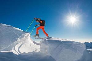 Ein Mann, der Alpinskifahrer auf Skiern und Robbenfellen in so viel Schnee mit Hindernissen klettert foto