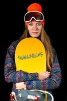 blondes Mädchen mit langen Haaren mit Snowboard und Wintersportbekleidung und Skimaske im Studio foto