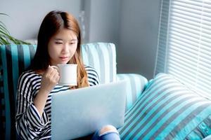 junge asiatische Frau, die auf Laptop-Computer sitzt und Kaffee trinkt. foto