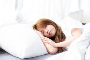 junge asiatische frau schlafen im bett liegend mit kopf auf kissen. foto