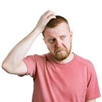Mann kratzt sich im Zweifel am Kopf foto