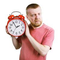 unglücklicher Mann mit rotem Wecker in der Hand foto