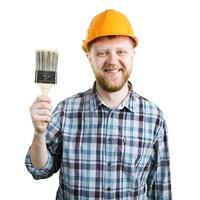 Mann in einem orangefarbenen Helm mit einer Bürste foto