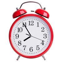 rote runde Uhr zeigt fünf Minuten vor acht foto