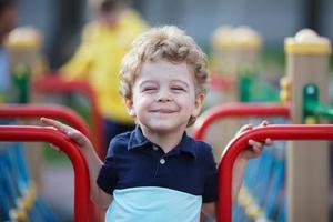 kleiner lockiger Junge, der Spaß lächelt foto