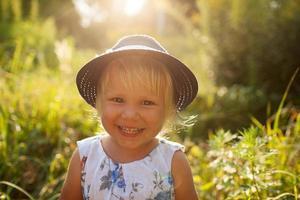 kleines blondes Mädchen mit blauem Hut foto