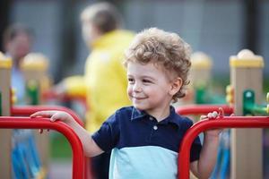 kleiner Junge spielt auf dem Spielplatz foto
