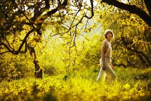 Frau, die im Sommerapfelgarten spazieren geht foto