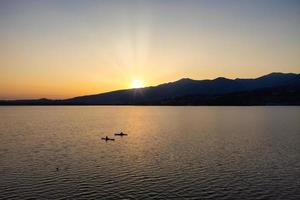 Silhouette von zwei Kajaks mitten im See bei Sonnenuntergang foto
