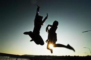 Silhouette glückliche Frau, die im Sonnenuntergang gegen schön springt. Freiheit, Genusskonzept. foto