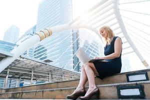 Geschäftsfrau, die mit Laptop im Freien arbeitet. Technologie und Glückskonzept. Beauty- und Lifestyle-Konzept. Stadt und urbanes Thema. Frau mit blonden Haaren, die Computer benutzt foto
