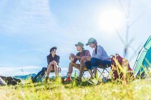 Gruppe von Reisenden, die im Vordergrund der Wiese campen und Picknick machen. Berg- und Seehintergrund. Menschen und Lebensstile Konzept. Outdoor-Aktivität und Freizeitthema. Backpacker- und Wanderer-Lifestyle foto