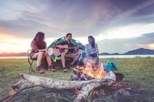 gruppe von reisenden, die campen und picknicken und zusammen musizieren. Berg- und Seehintergrund. Menschen und Lebensstil. Outdoor-Aktivität und Freizeitthema. Rucksacktourist und Wanderer. Morgen- und Abenddämmerung foto