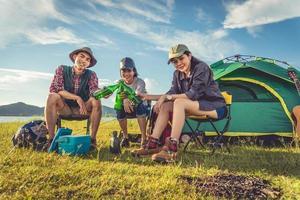 Gruppe von Reisenden, die campen und Picknick auf der Wiese mit Zeltvordergrund machen. Berg- und Seehintergrund. Menschen und Lebensstile Konzept. Outdoor-Aktivität und Freizeitthema. Backpacker- und Wanderer-Thema foto