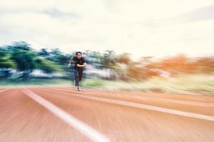 Laufender Mann, der auf der Strecke mit radialer Unschärfe, Sport- und Aktivitätskonzept läuft foto