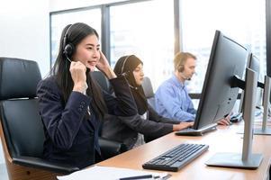 Gruppe junger Berufs-Call-Center-Betreiber mit Headsets, die im Büro arbeiten. Business-Telemarketing-Service-Mitarbeiter, die sich auf die Gesprächsarbeit konzentrieren und kundenfreundlich sprechen foto