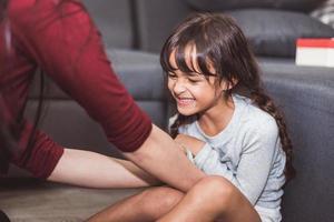 Kaukasisches kleines Mädchen von Mutter im Wohnzimmer gekitzelt. Menschen Lifestyle und Kinderkonzept foto