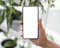 Frau, die Smartphone mit Kopienraum hält foto