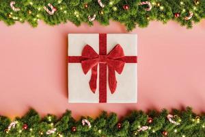 Geschenk mit Schleife und Weihnachtsgirlanden herum foto
