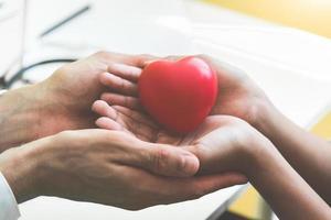 Doktorhände, die dem Patienten rotes Massageherz halten und geben foto
