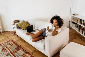 schwarze junge Frau mit Handy beim Ausruhen auf dem Sofa foto