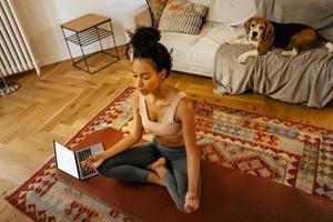 Schwarze junge Frau, die während der Yogapraxis mit ihrem Hund meditiert foto
