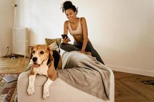 Schwarze junge Frau mit Handy beim Sitzen mit ihrem Hund auf dem Sofa foto