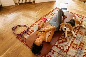 schwarze junge Frau mit Handy beim Ausruhen nach der Yogapraxis foto