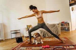 Schwarze junge Frau, die während der Yogapraxis mit ihrem Hund Sport macht foto