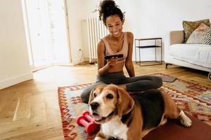 Schwarze junge Frau mit Handy beim Sitzen mit ihrem Hund auf der Matte foto