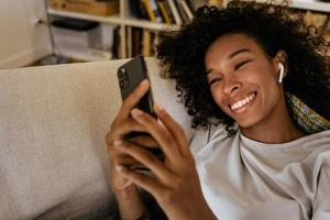 Schwarze junge Frau in Kopfhörern mit Handy beim Ausruhen auf dem Sofa foto