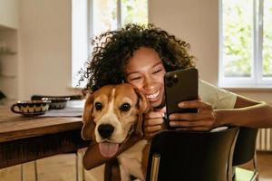 Schwarze junge Frau umarmt sich mit ihrem Hund, während sie das Handy benutzt foto