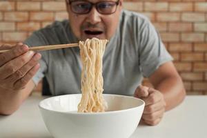 hungriger lässiger thailändischer mann auf dem backsteinmauerhintergrund verwendet essstäbchen, um während der mittagspausen heiße Instantnudeln in weißer tasse zu essen, schnell, lecker und billig. traditionelle asiatische Fast-Food-Küche. foto
