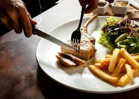 Messerschneiden gegrilltes Schweinekotelett Steak Nahaufnahme, Schweinekotelett Steak mit Salat und Pommes frites foto