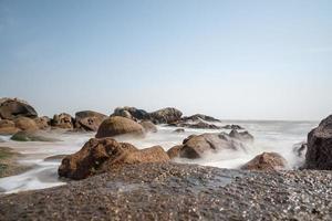 die weißen Wellen schlagen gegen die schwarzen Felsen foto