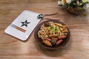 eine Schüssel Nudelsuppe mit Wurst, Gemüse und Fleisch steht auf dem Tisch foto