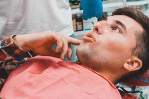 Der Patient erzählt dem Zahnarzt von den schmerzenden Zahnschmerzen. foto