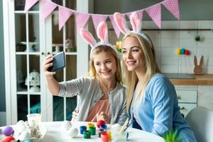 Mama und Tochter machen Selfies in den Osterhasenohren. foto
