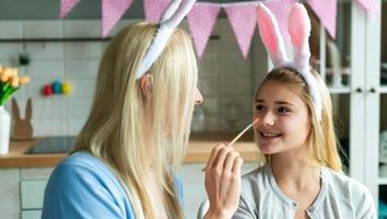Mutter und Tochter mit Hasenohren-Stirnbändern und bemalten Ostereiern zu Hause foto