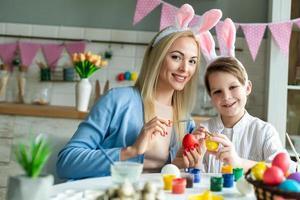 lustige, fröhliche, freudige Mutter unterrichten, ihren kleinen Sohn trainieren, zeichnen, bemalen, Ostereier dekorieren, zusammen Hasenohren tragen, sich auf Ostern vorbereiten foto