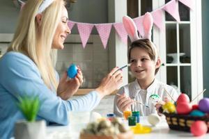 Mutter und Sohn mit Hasenohren-Stirnbändern und bemalten Ostereiern zu Hause foto