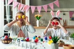 kleine, positive, fröhliche Schwester und ihr Bruder, die sich auf Ostern vorbereiten, am Schreibtisch sitzen, bunte, bemalte Eier auf die Augen halten foto