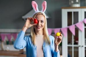 eine junge, fröhliche Frau in den Ohren des Hasen hat ein bemaltes Osterei auf ihr Auge gelegt foto