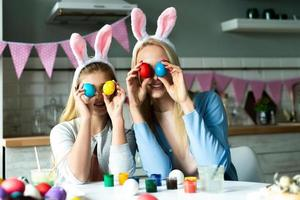 kleine, positive, fröhliche Tochter und ihre Mutter, die sich auf Ostern vorbereiten, am Schreibtisch sitzen, bunte, bemalte Eier auf die Augen halten foto