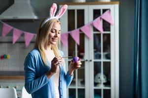 schöne, lächelnde Blondine in Hasenohren färbt Osterei, bereitet sich auf Ostern vor foto