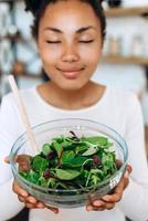 Süße, junge Frau, die mit geschlossenen Augen einen köstlichen Salat hält und den Moment genießt. Konzept der gesunden Ernährung foto
