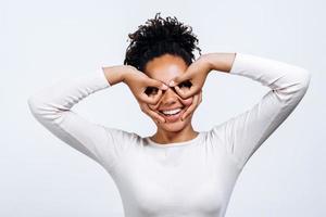 Porträt einer positiven und emotionalen schönen jungen Frau, die aus Fingern eine Figur ähnlich der Pilotenbrille um ihre Augen isoliert auf einer weißen Wand gemacht hat. foto