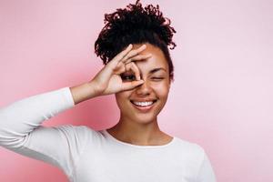 Mädchen mit weicher, glatter, sauberer Haut, strahlendem Lächeln, gestikulierendes OK-Zeichen in der Nähe eines Auges einzeln auf rosafarbenem Hintergrund foto